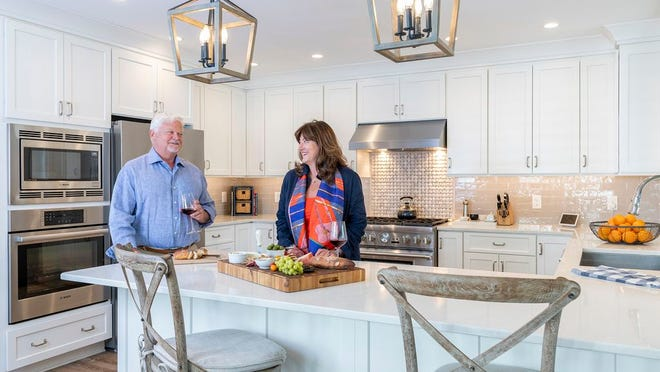 Lisa and Rick Morrison entertain often around the open kitchen, which features Tedd Wood cabinets from Riverhead Building Supply.