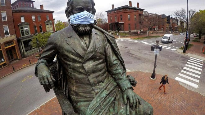 A statue off literary great Henry Wadworth Longfellow wears a coronavirus mask in Portland, Maine, May 18.
