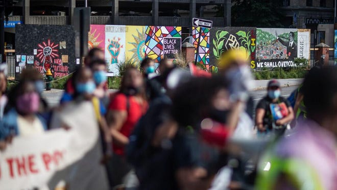 A youth organized Juneteenth protest marches past murals painted in the wake of recent demonstrations across the country, Friday, June 19, 2020, in Providence. Juneteenth commemorates when the last enslaved African Americans learned they were free 155 years ago. Now, with support growing for the racial justice movement, 2020 may be remembered as the year the holiday reached a new level of recognition.