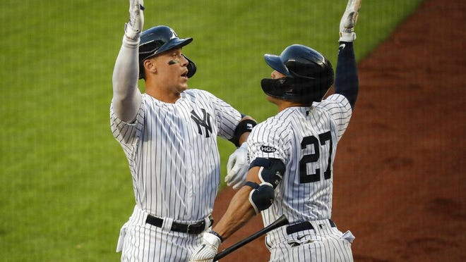 New York's Aaron Judge, left, celebrates with Giancarlo Stanton after hitting a solo home run off  Red Sox starting pitcher Zack Godley during the first inning Saturday in New York.