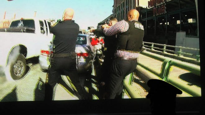 The photograph is taken from a body-camera video released by the Providence Police of the scene as police officers shoot into the white pickup driven by Joseph Santos as it rams a car in front of it.