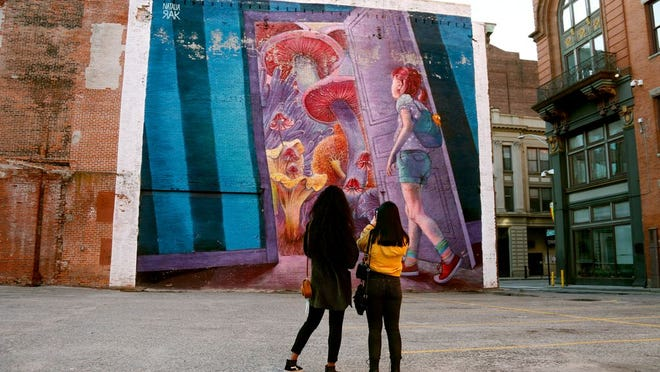 """PVDFest Virtual Scavenger Hunt announced locations and corresponding tasks to complete by August 17. In March, students Sylvia Amefia of Providence College and her friend Claudia Comczyk, of Assumption College, admire the large mural, """"Adventure Time,"""" by Natalia Rak, painted as part of the 2015 arts festival."""