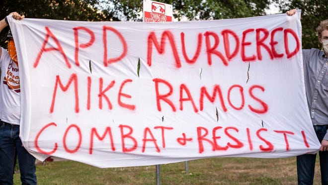 """Protesters hold up a sign that reads """"APD Murdered MIke Ramos Combat & Resist"""" during a protest on Saturday, April 25, 2020. A man was shot and killed during a police involved shooting Friday night. Many have condemned the shooting as unwarranted. Sergio Flores For AMERICAN-STATESMAN"""
