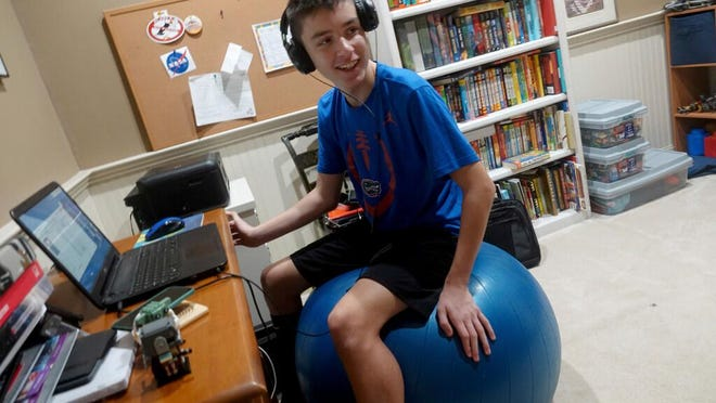 In this Aug. 31, 2020, file photo, Andrew Burstein, 13, logs onto 8th grade class with Don Estridge High Tech Middle School from his home in Delray Beach, Fla., during the first day back for Palm Beach County Schools. Burstein said it took about an hour to log into school but after the delay he had no issues.