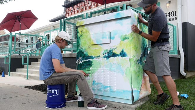 Jadon Schwahn (left) and Cody Meendering, both with Clean Slate Group, install vinyl panels with artwork by Ellie DiRutigliano onto a traffic-signal box at High Street and Oakland Park Avenue on Sept. 10. The long-in-the-works project also saw similar pieces by local artists installed at High Street's intersections with Como Avenue, Kanawha Avenue, Hollenback Road and Henderson Road.