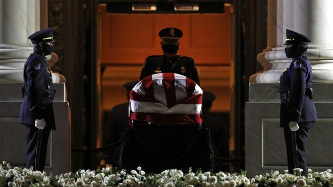 Members of a U.S. Capitol Police honor guard stand in front of the flag-draped casket of Rep. John Lewis, D-Ga., as he lies in state on the East Front Steps of the Capitol in Washington, Monday, July 27, 2020.