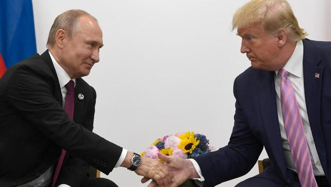 """In this June 28, 2019, file photo President Donald Trump, right, shakes hands with Russian President Vladimir Putin, left, during a bilateral meeting on the sidelines of the G-20 summit in Osaka, Japan. Trump says he has """"never discussed"""" with Putin reports the Russians paid bounties to Taliban rebels for killing U.S. troops in Afghanistan."""
