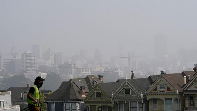 """A worker cleans grass at Alamo Square Park as a mix of smoke from wildfires and fog obscures the skyline above the """"Painted Ladies,"""" a row of historical Victorian homes in San Francisco on Monday. Smoke from the fires has reached and New England and Europe."""