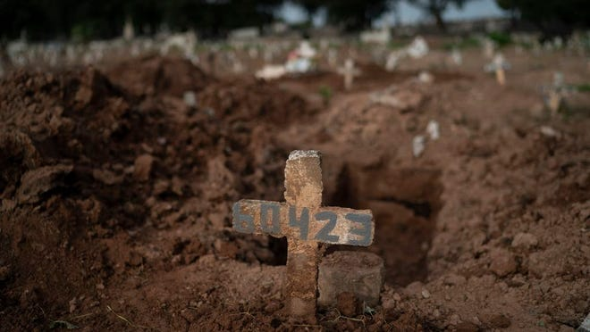 """A cross marks the grave of 57-year-old Paulo Jose da Silva, who died from the new coronavirus, in Rio de Janeiro, Brazil, Friday, June 5, 2020. According to Monique dos Santos, her stepfather mocked the existence of the virus, didn't use a mask, didn't take care of himself, and wanted to shake hands with everybody. """"He didn't believe in it and unfortunately he met this end. It's very sad, but that's the truth,"""" she said."""