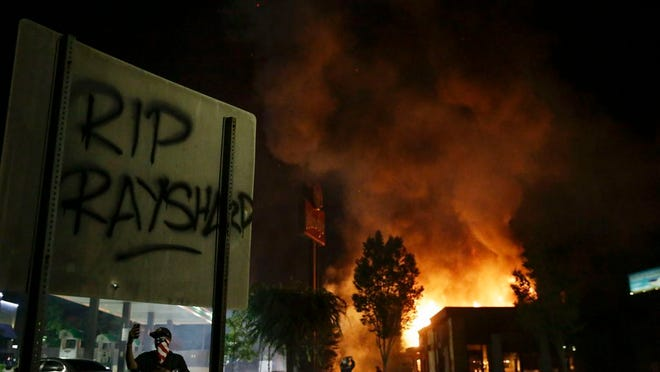"""""""RIP Rayshard"""" is spray painted on a sign as as flames engulf a Wendy's restaurant during protests Saturday, June 13, 2020, in Atlanta. The restaurant was where Rayshard Brooks was shot and killed by police Friday evening following a struggle in the restaurant's drive-thru line."""