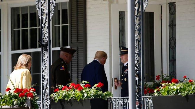 President Donald Trump, second from right, enters the Superintendent's House accompanied by Superintendent of the United States Military Academy Lt. Gen. Darryl Williams, second from right, and his wife Erin Williams, left, at the United States Military Academy in West Point, N.Y., Saturday, June 13, 2020.
