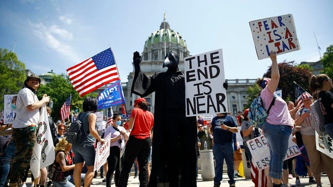 In this Friday, May 15, 2020 file photo, protesters hold a rally against Pennsylvania's coronavirus stay-at-home order at the state Capitol in Harrisburg, Pa.