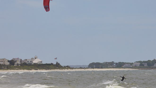 A kiteboarder rides Craigville Beach waves on a windy Thursday afternoon.