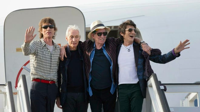 In this March 24, 2016 file photo, members of The Rolling Stones, from left, Mick Jagger, Charlie Watts, Keith Richards and Ron Wood pose for photos from their plane at Jose Marti international airport in Havana, Cuba. The Rolling Stones are threatening U.S. President Donald Trump with legal action for using their songs at his reelection campaign rallies despite cease-and-desist directives, according to a statement issued by the band Sunday June 28, 2020.
