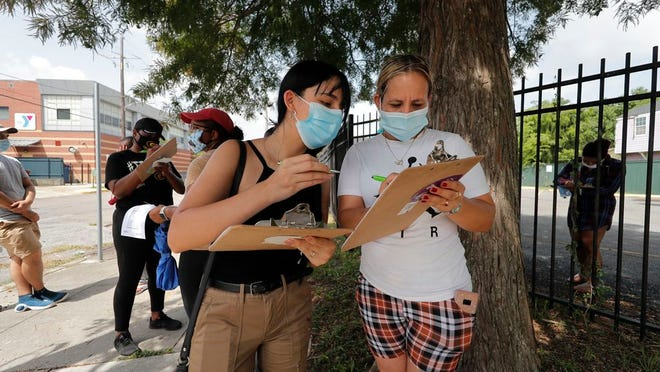 Edif Madrid, right, and Rosa Guillen wait in a line for COVID-19 testing at a mobile testing site in New Orleans, Wednesday, July 8, 2020. Testing sites in New Orleans have been running out of their daily allocation of tests within minutes of opening.