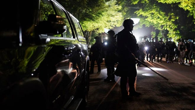 Portland police officers walk through the Laurelhurst neighborhood after dispersing protesters from the Multnomah County Sheriff's Office early in the morning on Saturday, Aug. 8, 2020 in Portland, Ore.