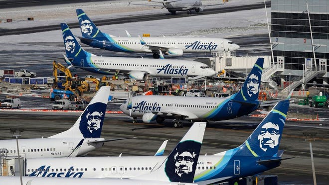 In this Feb. 5, 2019, file photo, Alaska Airlines planes are parked at a gate area at Seattle-Tacoma International Airport in Seattle. Alaska Airlines said over 300 employees among the company's workforce in Anchorage may lose their jobs on Oct. 1, 2020. The company said the Anchorage layoffs are part of company-wide job cuts because of the economic fallout from the coronavirus pandemic, Alaska Public Media reported Tuesday, Aug. 4.