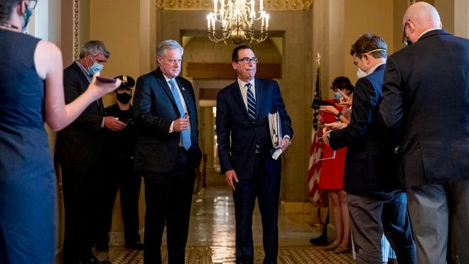 Treasury Secretary Steven Mnuchin, right, accompanied by White House chief of staff Mark Meadows, left, take a question from a reporter following a meeting with Senate Majority Leader Mitch McConnell of Ky. as negotiations continue on a coronavirus relief package on Capitol Hill in Washington, Tuesday, Aug. 4, 2020.