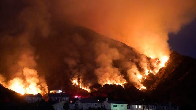The Ranch Fire burns over a residential area, Thursday, Aug. 13, 2020, in Azusa, Calif. Heat wave conditions were making difficult work for fire crews battling brush fires and wildfires across Southern California.