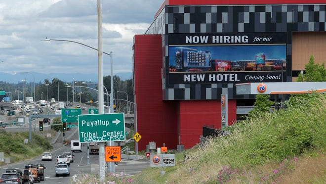 "In this July 9, 2020, file photo, a large video display reads ""Now hiring for our new hotel coming soon!,"" at the new Emerald Queen Casino, which is open, and owned by the Puyallup Tribe of Indians, in Tacoma, Wash. The United States added 1.8 million jobs in July, a pullback from the gains of May and June and evidence that the resurgent coronavirus has weakened hiring and the economic rebound."