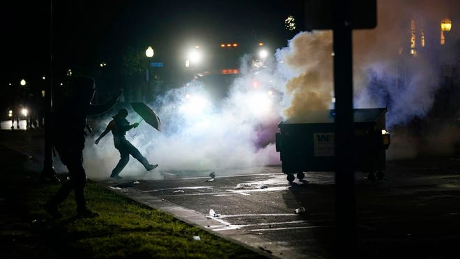 A protester kicks a smoke canister Tuesday, Aug. 25, 2020 in Kenosha, Wis. Anger over the Sunday shooting of Jacob Blake, a Black man, by police spilled into the streets for a third night.