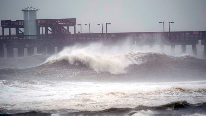 Waves crash near a pier, at Gulf State Park, Tuesday, Sept. 15, 2020, in Gulf Shores, Ala. Hurricane Sally is crawling toward the northern Gulf Coast at just 2 mph, a pace that's enabling the storm to gather huge amounts of water to eventually dump on land.