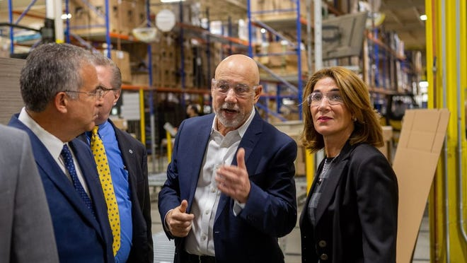 AIS President Bruce Platzman tours Lt. Gov. Karyn Polito around the company's office furniture factory in Leominster.