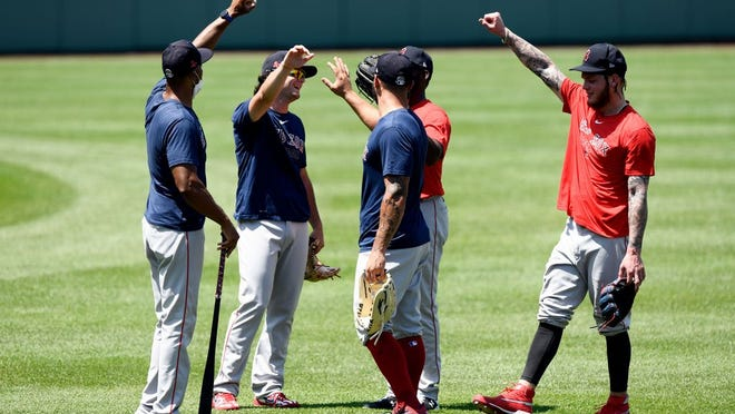 Red Sox outfielders Andrew Benintendi (16), Jackie Bradley Jr. (19), Kevin Pillar (5), and Alex Verdugo (99) have a distanced hands-in during practice at Fenway Park on Sunday.