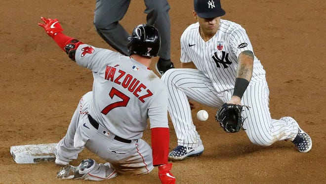 New York Yankees shortstop Gleyber Torres loses the ball as Boston Red Sox's Christian Vazquez (7) arrives with a double during the ninth inning of Sunday's game.