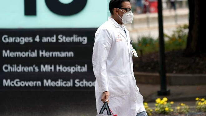 A healthcare professional walks through the Texas Medical Center Thursday, June 25, 2020, in Houston. The leaders of several Houston hospitals said they were opening new beds to accommodate an expected influx of patients with COVID-19, as coronavirus cases surge in the city and across the South.
