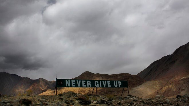 In this Sept. 14, 2017, file photo, a banner erected by the Indian army stands near Pangong Tso lake near the India-China border in India's Ladakh area. As the escalating and bitter military standoff between India and China protracts following their bloodiest confrontation in decades in the Ladakh region in 2020, experts warn the two nuclear-armed countries can unintentionally slide into a war over the roof of the world. The two most populous nations share thousands of kilometers (miles) disputed border and have accused each other for opening new fronts.