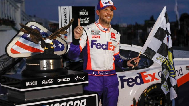 Denny Hamlin smiles after winning the NASCAR Cup Series auto race at Pocono Raceway on Sunday.