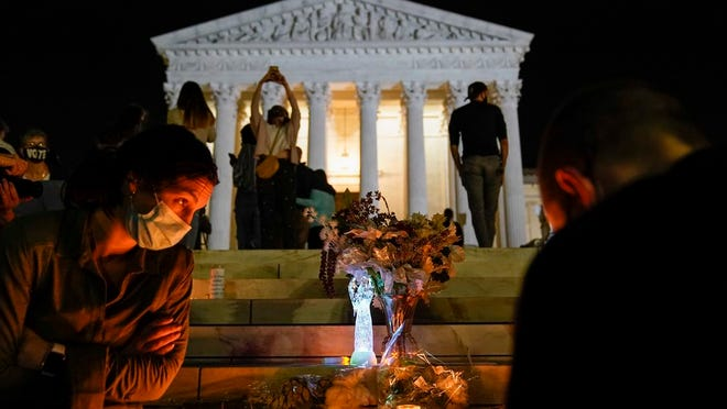 People gather at the Supreme Court Friday, Sept. 18, 2020, in Washington, after the Supreme Court announced that Supreme Court Justice Ruth Bader Ginsburg died of metastatic pancreatic cancer at age 87.