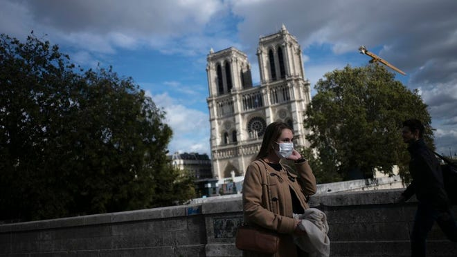 A woman walks by Notre Dame cathedral Saturday Sept.26, 2020 in Paris. While France suffered testing shortages early in the pandemic, ramped-up testing since this summer has helped authorities track a rising tide of infections across the country. More than 15,000 new cases were reported Friday, and the Paris hospital system is starting to delay some non-virus surgeries to free up space for COVID-19 patients.