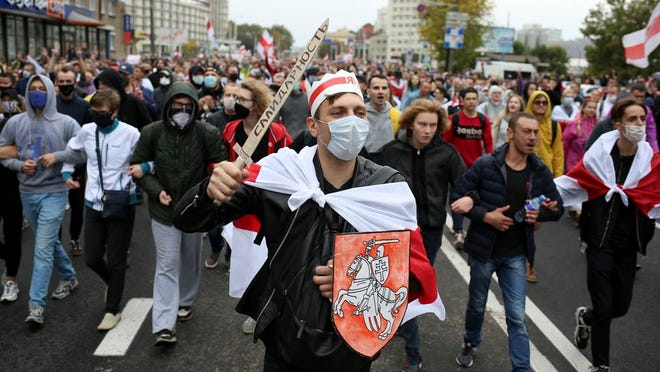 "Demonstrators, one of them wearing an old Belarusian nation flag and holding a cardboard sword reading ""solidarity"" march during an opposition rally to protest the official presidential election results in Minsk, Belarus, Sunday, Sept. 27, 2020. Hundreds of thousands of Belarusians have been protesting daily since the Aug. 9 presidential election."