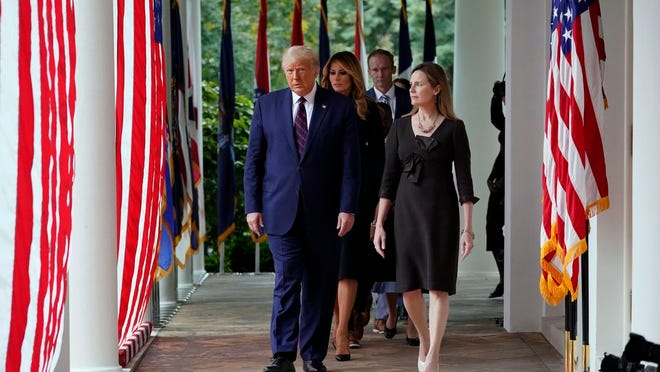 President Donald Trump walks along the Colonnade with Judge Amy Coney Barrett to a news conference to announce Barrett as his nominee to the Supreme Court, in the Rose Garden at the White House, Saturday, Sept. 26, 2020, in Washington.