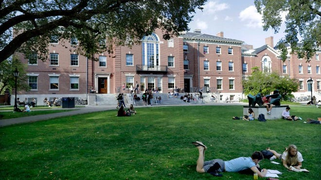 Students at Brown University enjoy a mild day to relax on the grass and read.