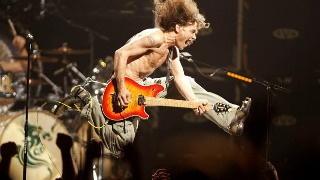 """Eddie Van Halen plays the final chord of """"Jump"""" during the Van Halen concert at the Continental Airlines Arena in East Rutherford, N,.J., in  2004. Eddie Van Halen, the guitar virtuoso whose blinding speed, control and innovation propelled his band Van Halen into one of hard rock's biggest groups, died Tuesday. Van Halen, who had battled cancer, was 65."""