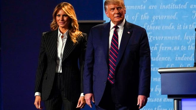 President Donald Trump stands on stage with first lady Melania Trump after the first presidential debate with Democratic presidential candidate former Vice President Joe Biden Tuesday, Sept. 29, 2020, at Case Western University and Cleveland Clinic, in Cleveland, Ohio. President Trump and first lady Melania Trump have tested positive for the coronavirus, the president tweeted early Friday.