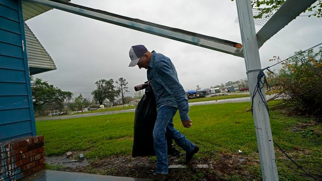 Jim Fontenot carries possessions into his brother's home, to which his family temporarily relocated to ride out Hurricane Delta which is expected to make landfall later in the day, in Lake Charles, La., Friday, Oct. 9, 2020.