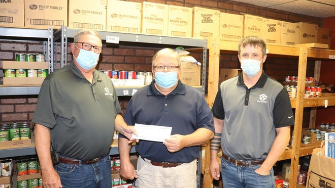 Doug Tauer (left) and Justin Wiese (right) of Central Bi-Products presented a donation to Dave Mumme of the food shelf.