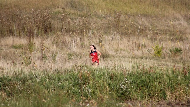 Olivia Stoterau tries to find her stride amongst the wild grass at Prairie View Golf Links near Worthington. She would go on to finish fifth for the Cards.