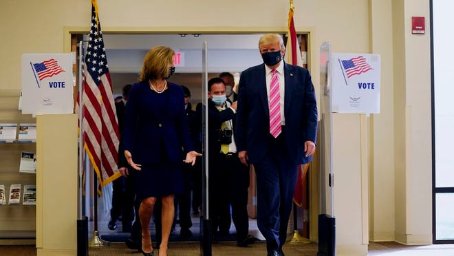 President Donald Trump walks with Wendy Sartory Link, Supervisor of Elections Palm Beach County, after casting his ballot for the presidential election, Saturday, Oct. 24, 2020, in West Palm Beach, Fla.