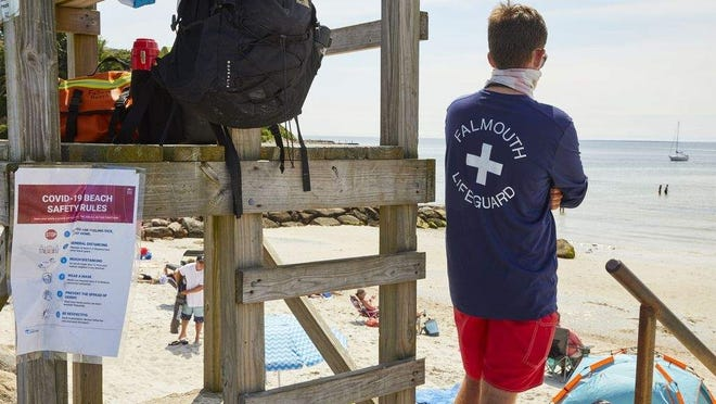 A July, 7, 2020, file photo shows a lifeguard standing at Old Silver Beach in Falmouth. A number of lifeguards who attended a party in Falmouth walked away infected by COVID-19.