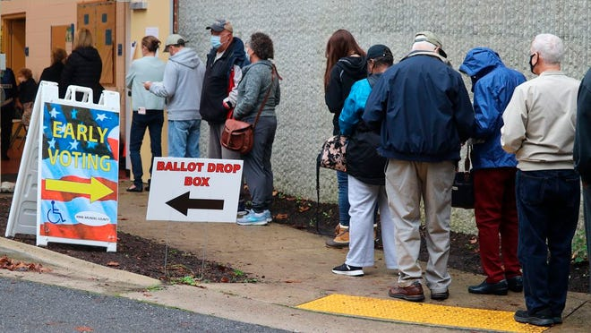 FILE - In this Monday, Oct. 26, 2020, file photo, voters wait in line to enter the Pip Moyer Recreation Center, in Annapolis, Md., on the first day of in-person early voting in the state. Tens of millions of Americans already cast ballots in the 2020 election amid record-breaking early voting during the coronavirus pandemic. But for some voters in a handful of states, casting an early ballot in-person isn't even an option.