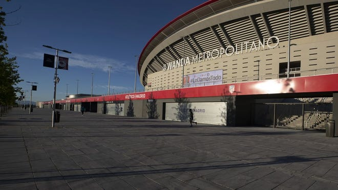 A man jogs past Atletico Madrid's Wanda Metropolitano stadium in Madrid, Spain, Tuesday, May 5, 2020. The Spanish soccer league aims to restart in June without spectators. It's new compulsory protocols say all players, coaches and club employees must be tested for COVID-19 coronavirus before training resumes, then regularly after that. All clubs' training facilities must be properly prepared and disinfected before players can start practicing individually.