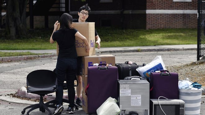 Freshman Feng Cong from Singapore and Cassie Lu from Thailand carry a box of their belongings to a pile as they move out of his dorm at Duke University in March.