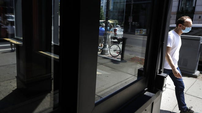 A pedestrian, right, walks past a storefront window, Tuesday in Boston.