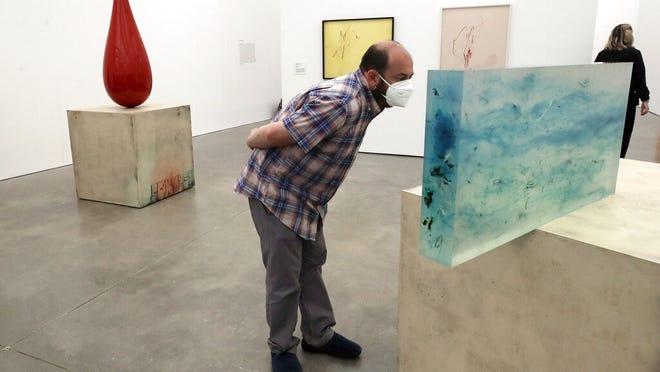 Museum visitor Jeffrey Gato, of Ashland, center, examines a sculpture by artist Sterling Ruby called ACTS/187 DREAMER, 2009, at the Institute of Contemporary Art, Tuesday in Boston.