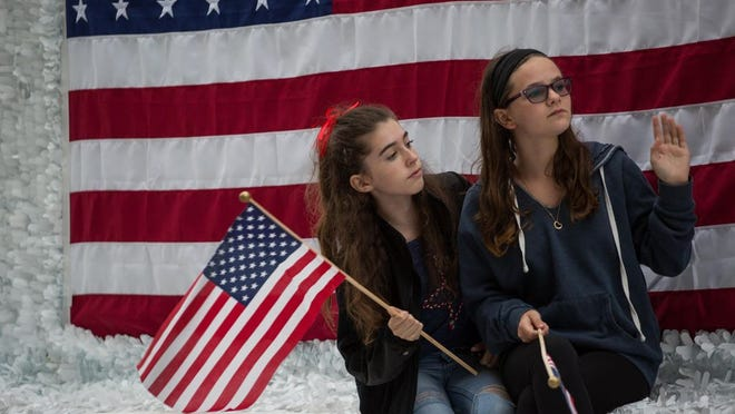 Two girls wave to parade attendees from a float, during the 65th annual Flag Day parade in Quincy, Massachusetts, on June 11, 2016.